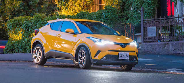 Toyota C-HR Exterior_ Sun Fusion front three quarter parked with LED headlamps on at night