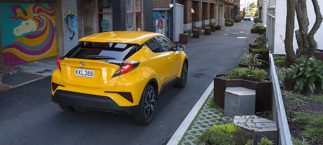 Toyota C-HR Exterior_ Sun Fusion high angle, rear profile navigating narrow town streets