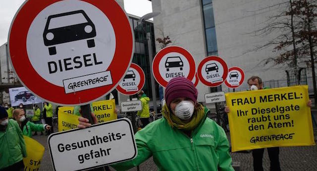 The sign in the foreground reads - 'Diesel is a health hazard'. The yellow sign reads - 'Mrs Merkel, their dieselgate robs us the breath'